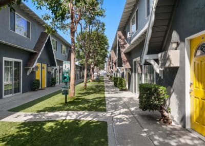 apartment walkway with trees and grass